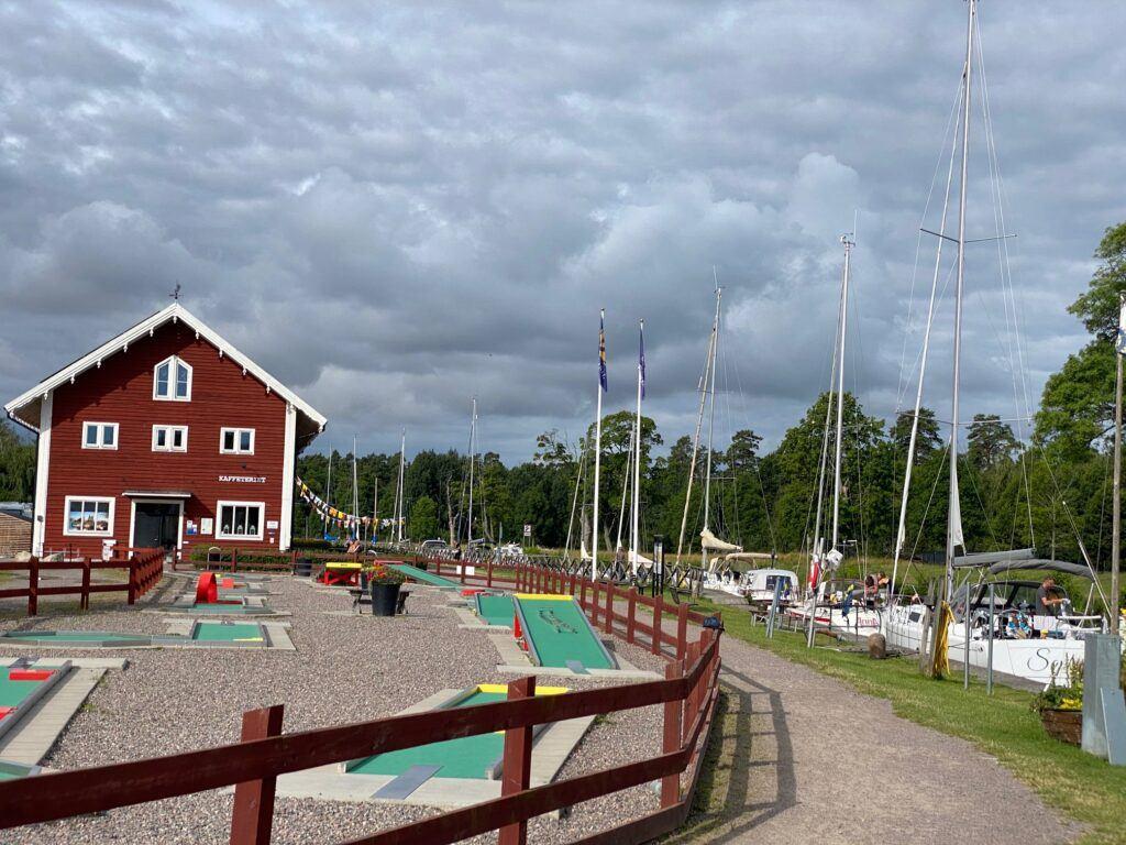 Minigolfbana intill kanalen där båtar ligger på rad