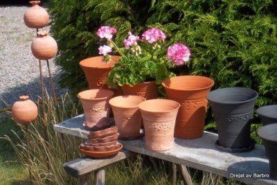 Foto på sex stycken drejade lerkrukor där en innehåller en rosa pelargon