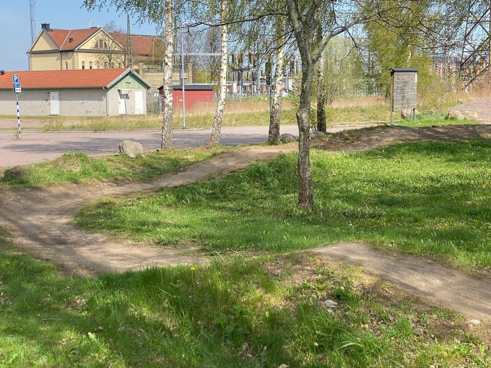 Slingrande cykelstig över gräsmatta.