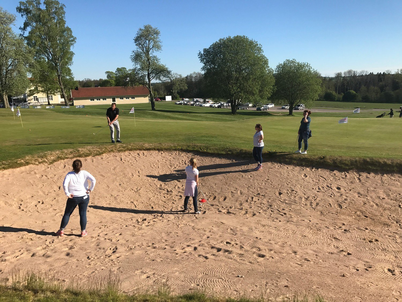 Golfspelare står i bunker på golfbana