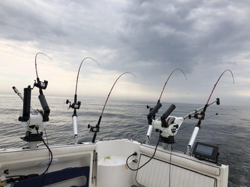 I förgrunden ser man en båt med fem olika fiskespön, i bakgrunden skymtar en lugn sjö, himlen har beslöjats med dramatiska moln.