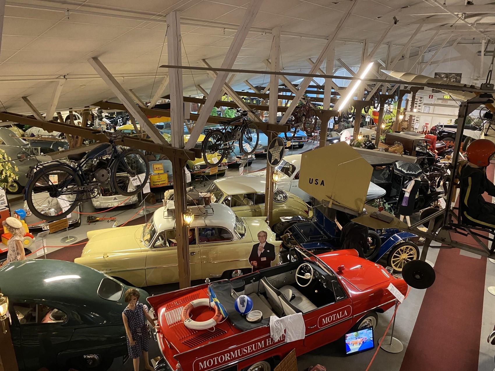 Foto taget uppifrån på en stor samling bilar som står fint uppradade, i taket hänger cyklar och mopeder. Samtliga fordon är mycket gamla.