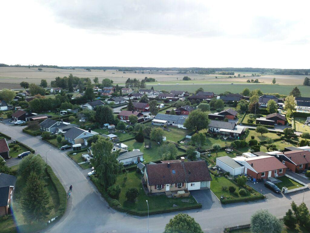 ett flygfoto där man ser en väg och flera villaområden