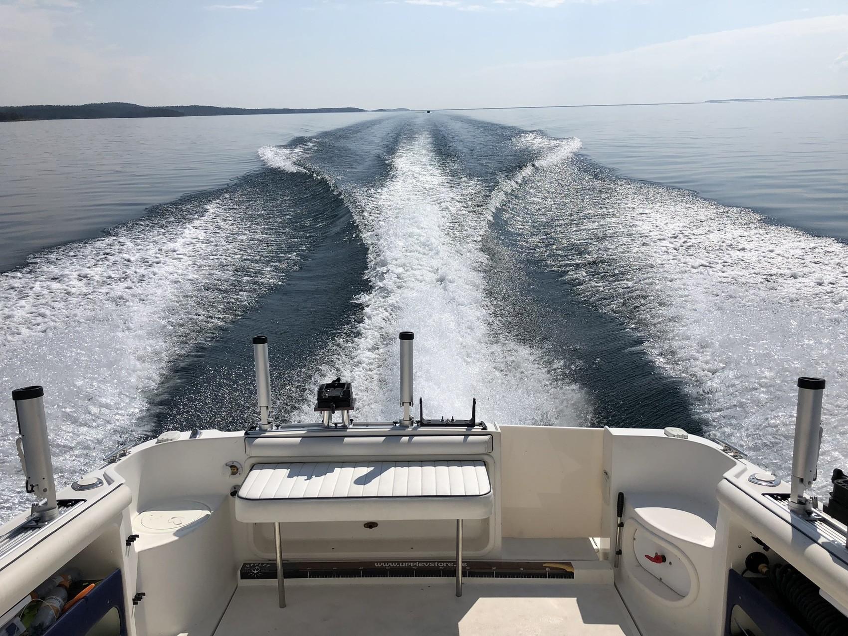 Man ser aktern på en liten men lyxig båt som forsar fram över en sjö, vattnet skummas så det blir som vita spår efter båten, sole skiner och himlen är blå.