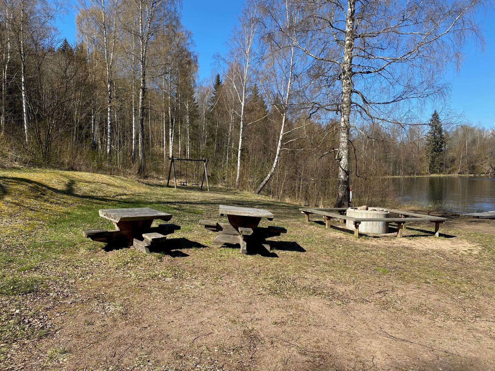 Grillplats på gräs med bord och gunga