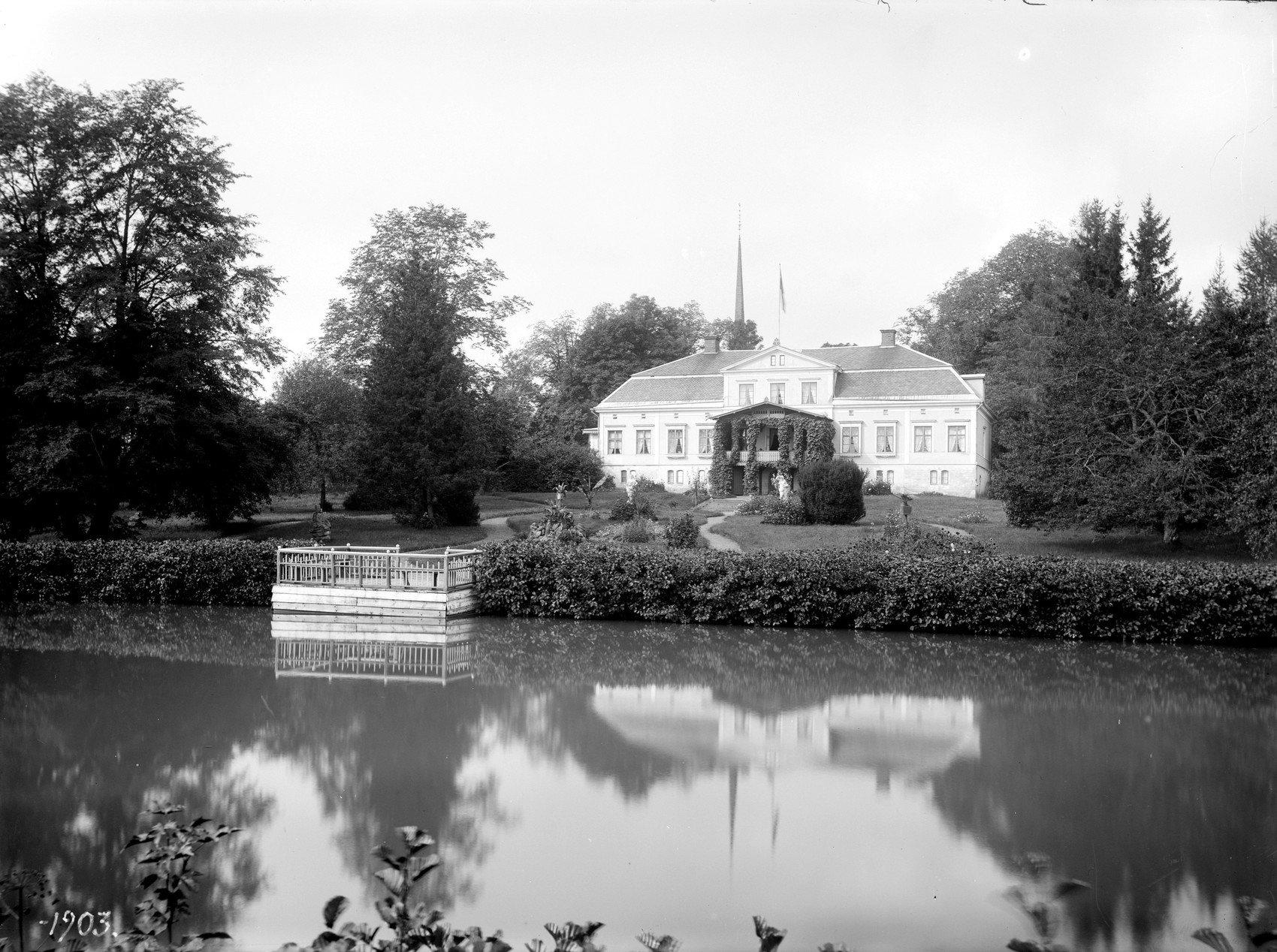 Svartvitt foto på en gårdsbyggnad precis bredvid vatten