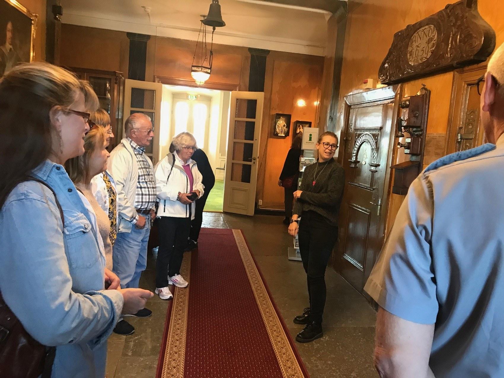Guide pratar inför åskådare i hall