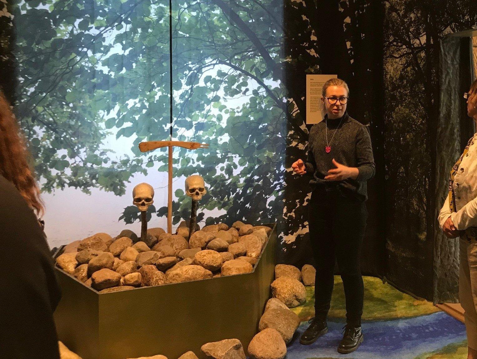 Guide står vid döskallar på museum och pratar