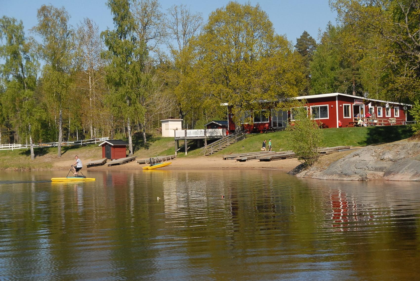 Bild på en sjö där en man sitter och cyklar på en gul båt