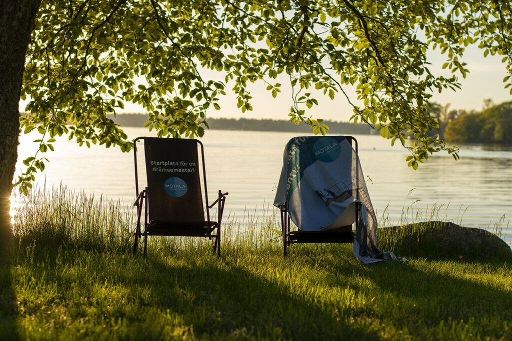 Två solstolar ståendes under ett grönskande träd, en sjö skymtar i bakgrunden