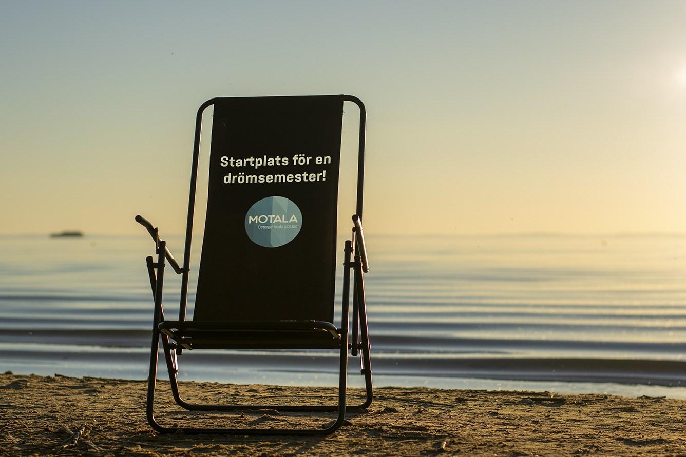 """En svart solstol med texen: """"Startplats för en drömsemester"""" ståendes i vattenbrynet, i solnedgång"""