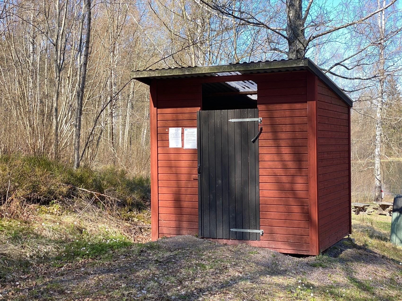 Röd liten byggnad med svart dörr