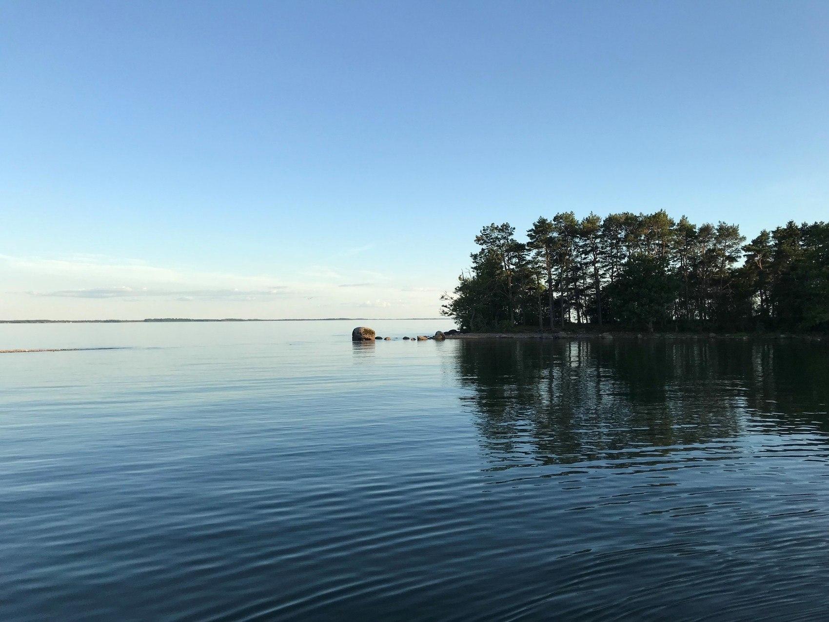 Skymning över ö en stilla sommarkväll