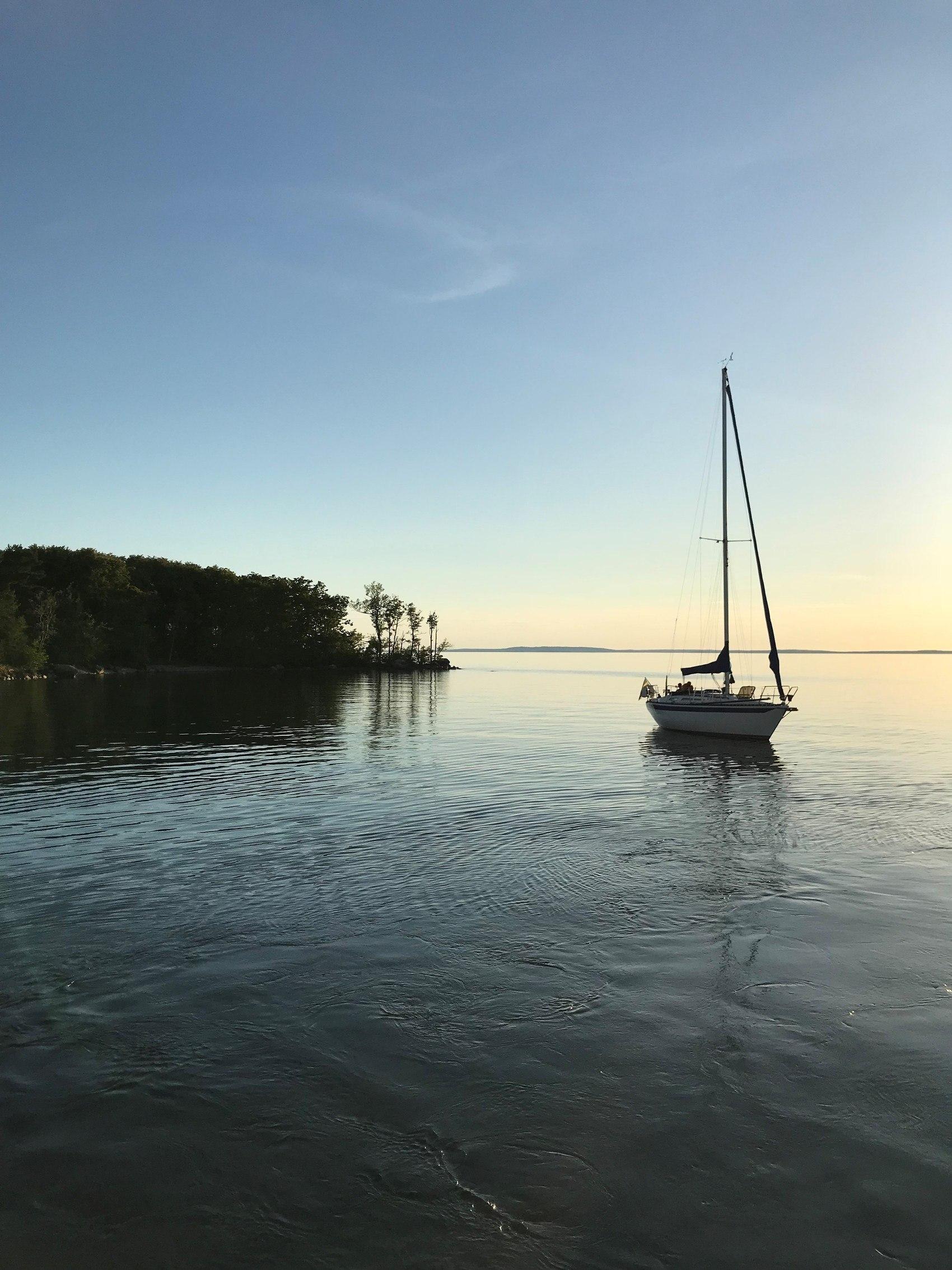 Segelbåt ligger förtöjd utanför ö en stilla sommarkväll.