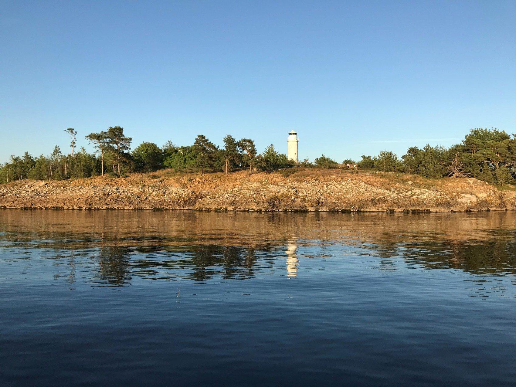 Foto taget från vattnet som visar ö med vit fyr.