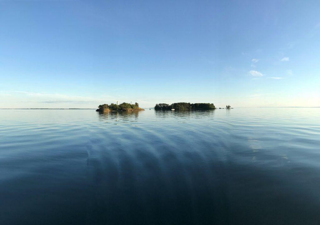 En ö syns på håll i vattnet. Himlen är klarblå och vattnet ligger stilla.