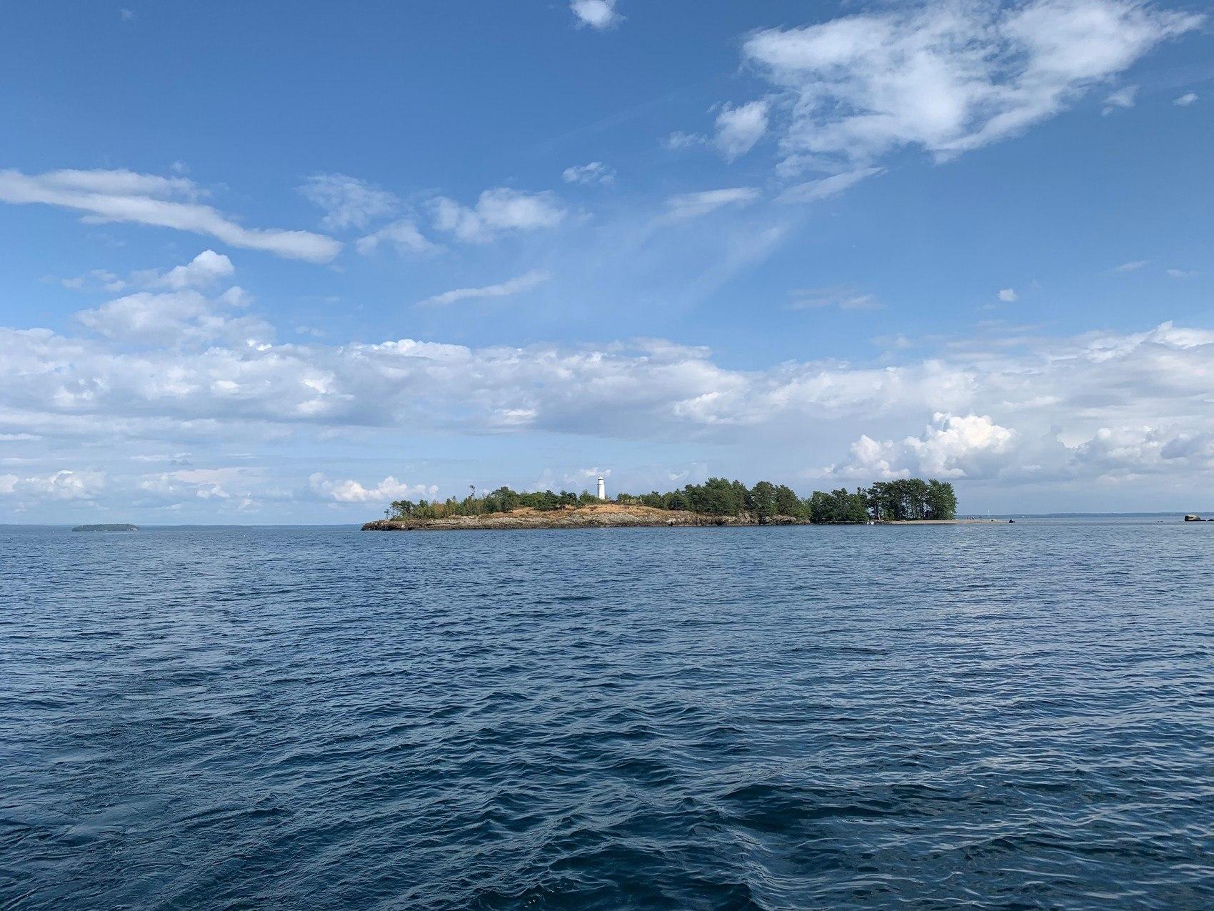 En ö omgiven av vatten och blå himmel