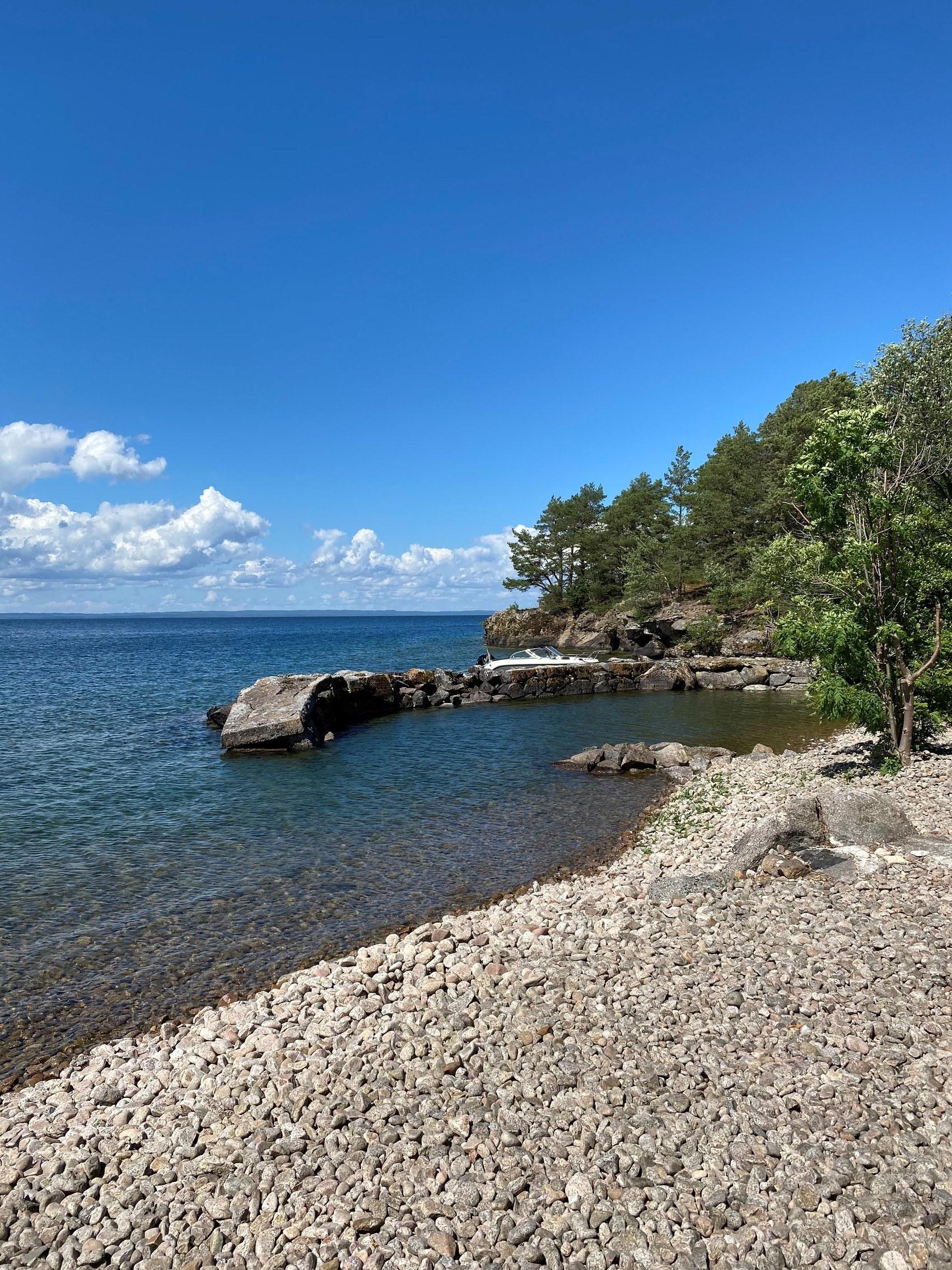 Strand med grå stenar