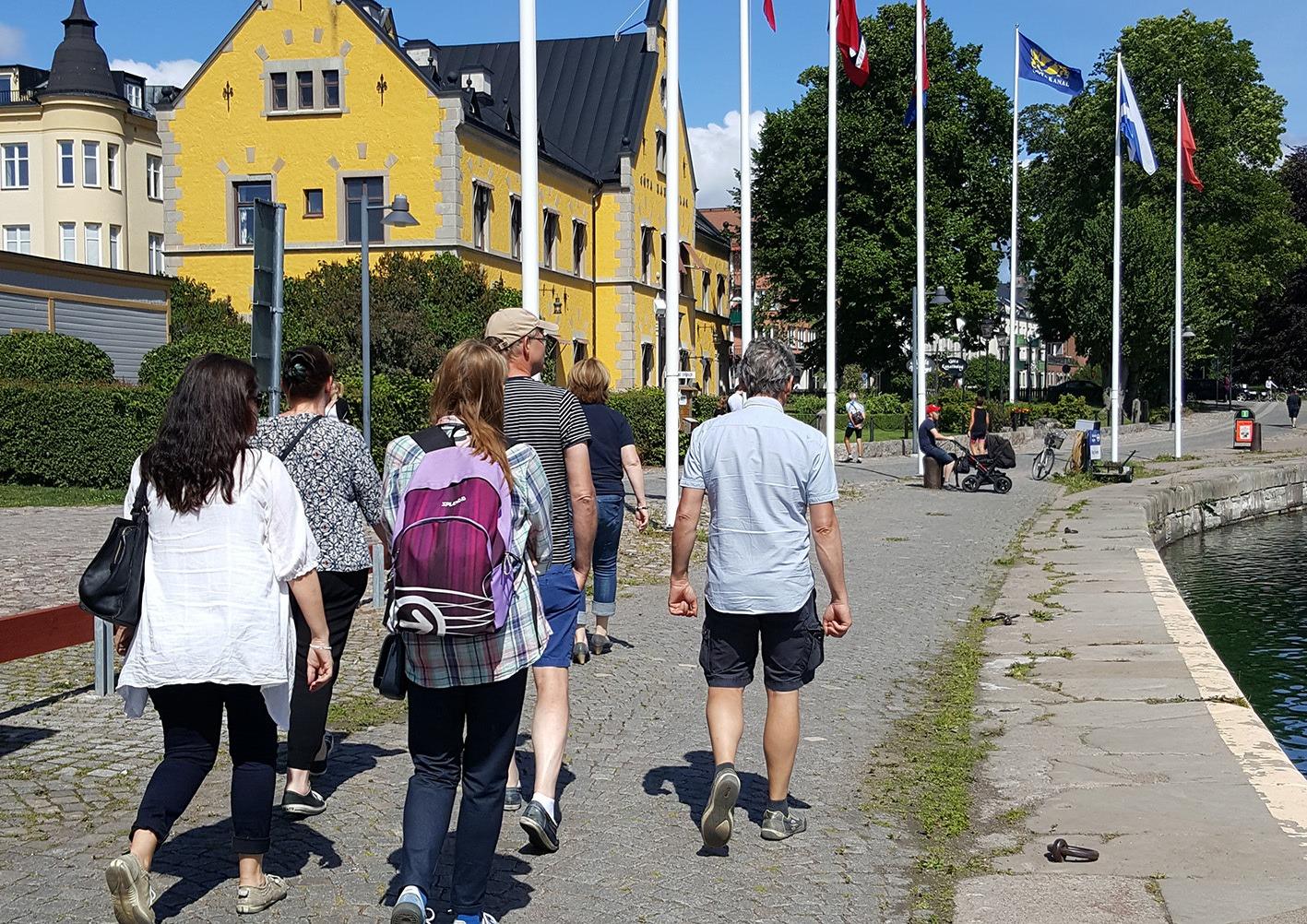 En samling människor som promenerar längs med en kaj.