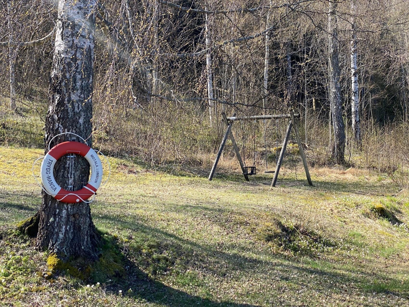 Gungställning på gräsplan. På ett träd hänger en livboj.