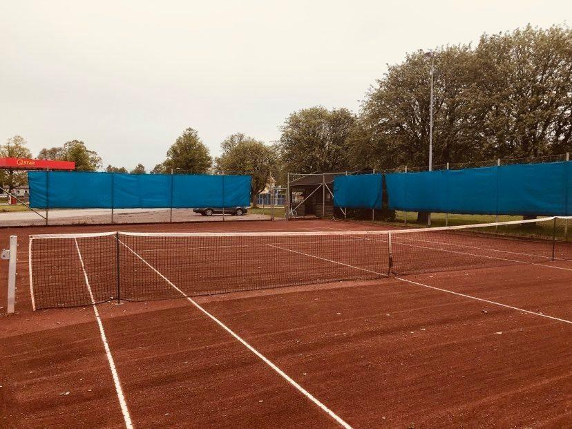 Foto av en brunröd tennisbana med vita linjer