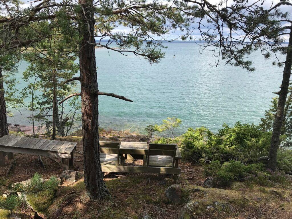 Vacker utsiktsplats med bord och trästolar. Vacker utsikt över vattnet.