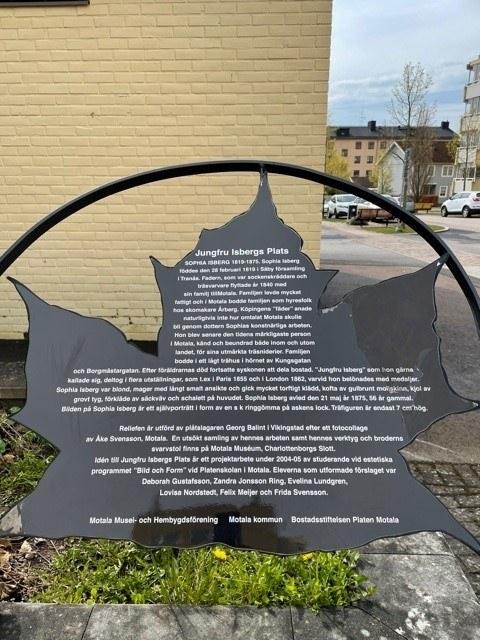 Ett grått metallöv med vit text som beskriver Jungfru Isbergs liv.