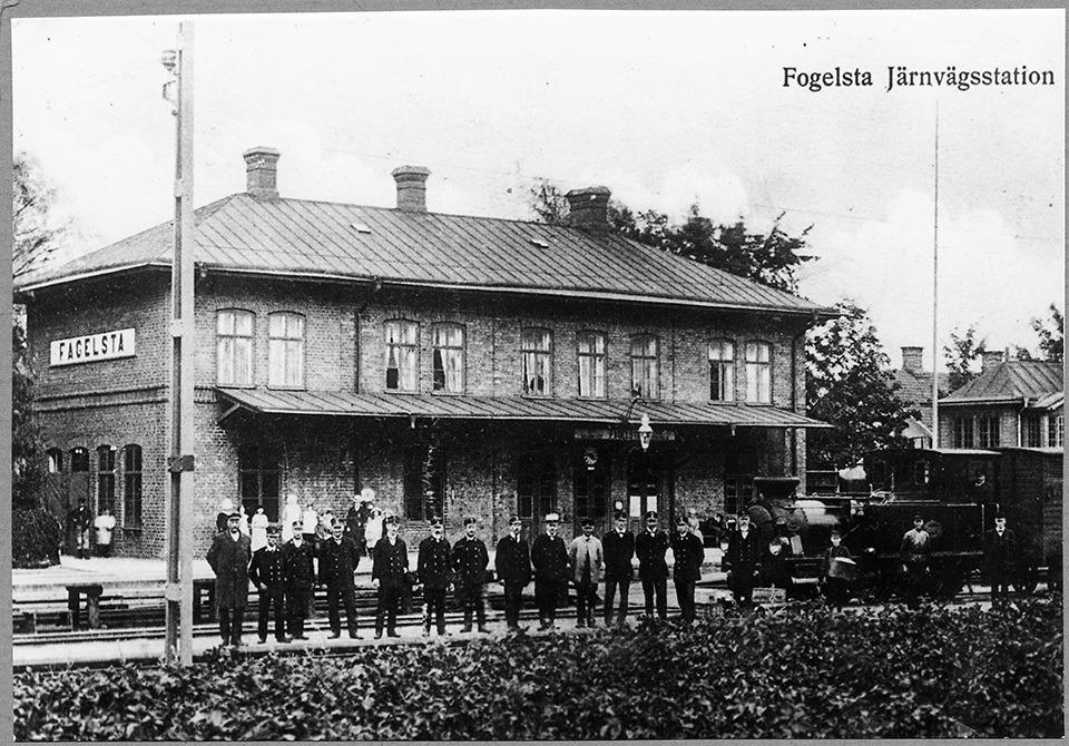 Ett svartvitt foto på en stationsbyggnad med ett tjugotal svartklädda män uppradade framför byggnaden