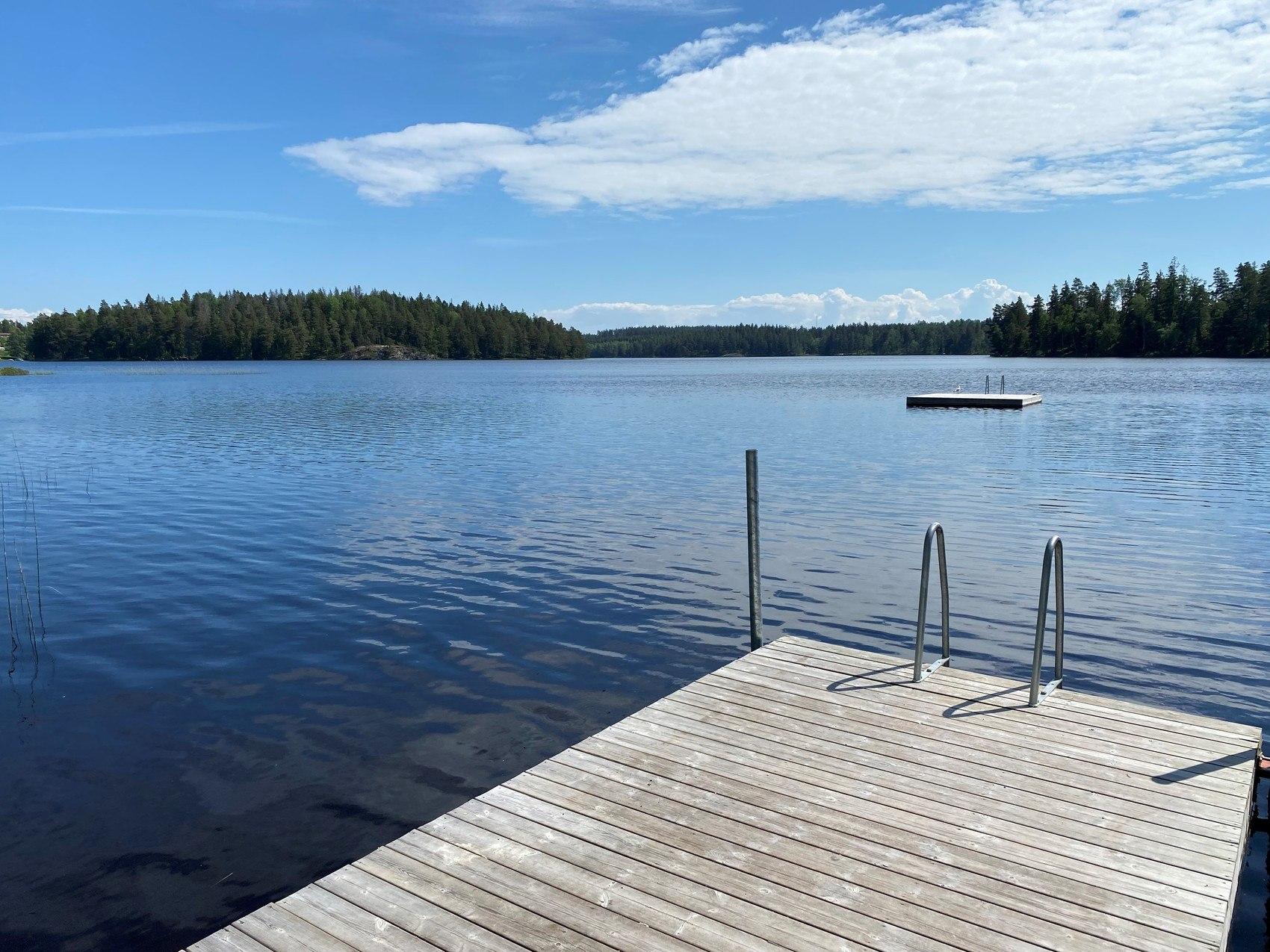 Delar av en brygga omgiven av en blå sjö i strålande solsken, i bakgrunden syns en flytbrygga.