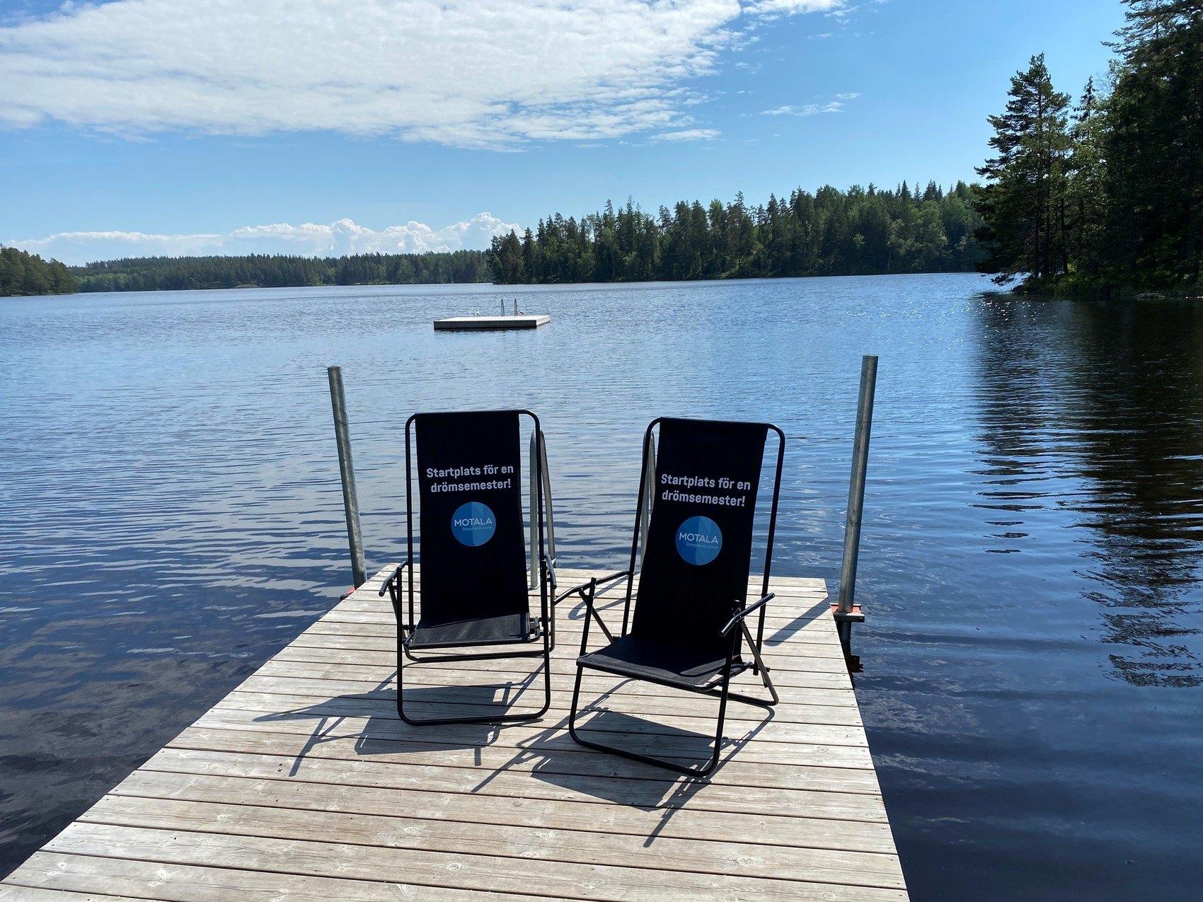 """Två svarta solstolar med texten """"Startplats för en drömsemester"""" ståendes på en brygga med en sjö i bakgrunden. En flytbrygga skymtas i bakgrunden."""