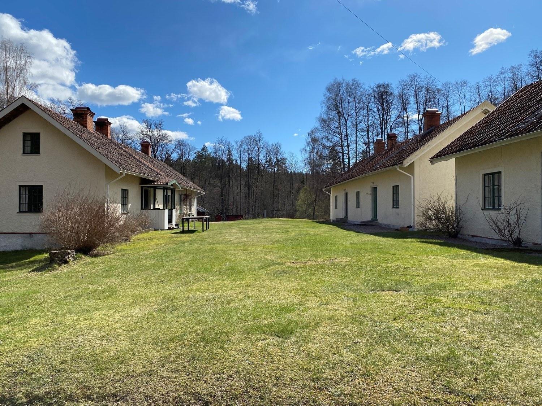 Äldre små gula huslängor på en gräsplan