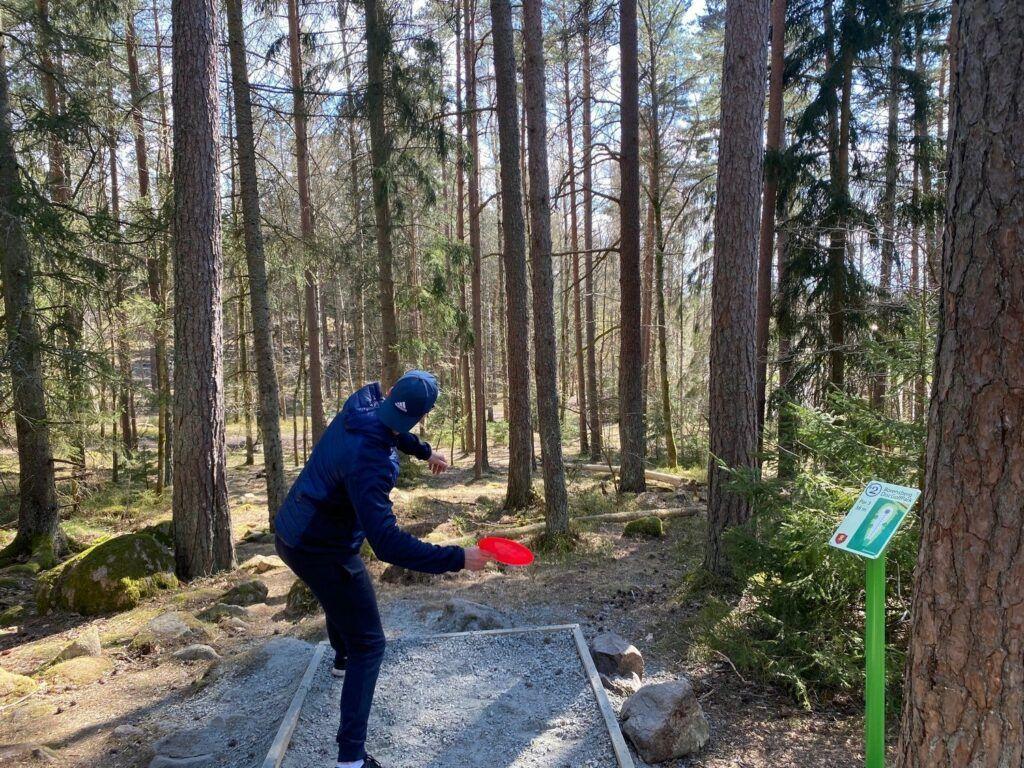 Person kastar iväg en röd frisbee