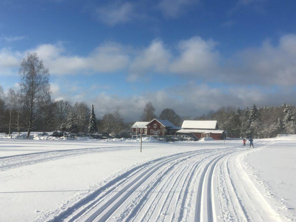 En vintervärld med knallblå himmel, vita moln och perfekta längdskidspår.