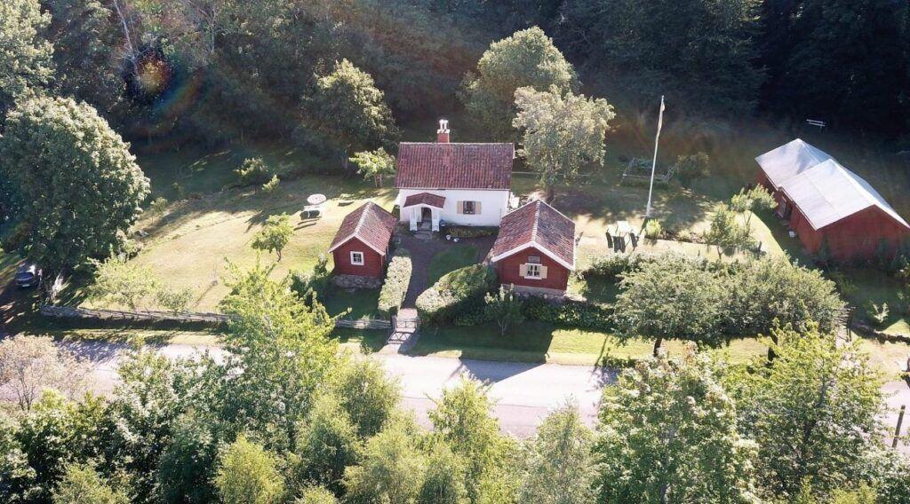 Foto ovanfrån på ett vit hus med några röda byggnader på tomten.