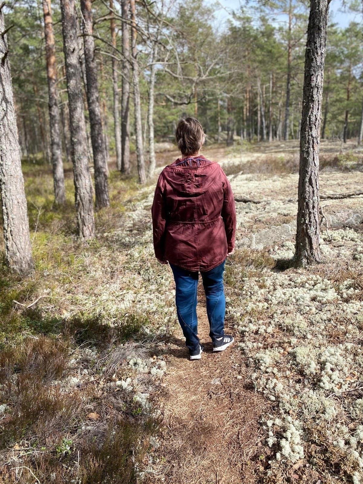 Person står i skogsområde med mycket vit mossa.