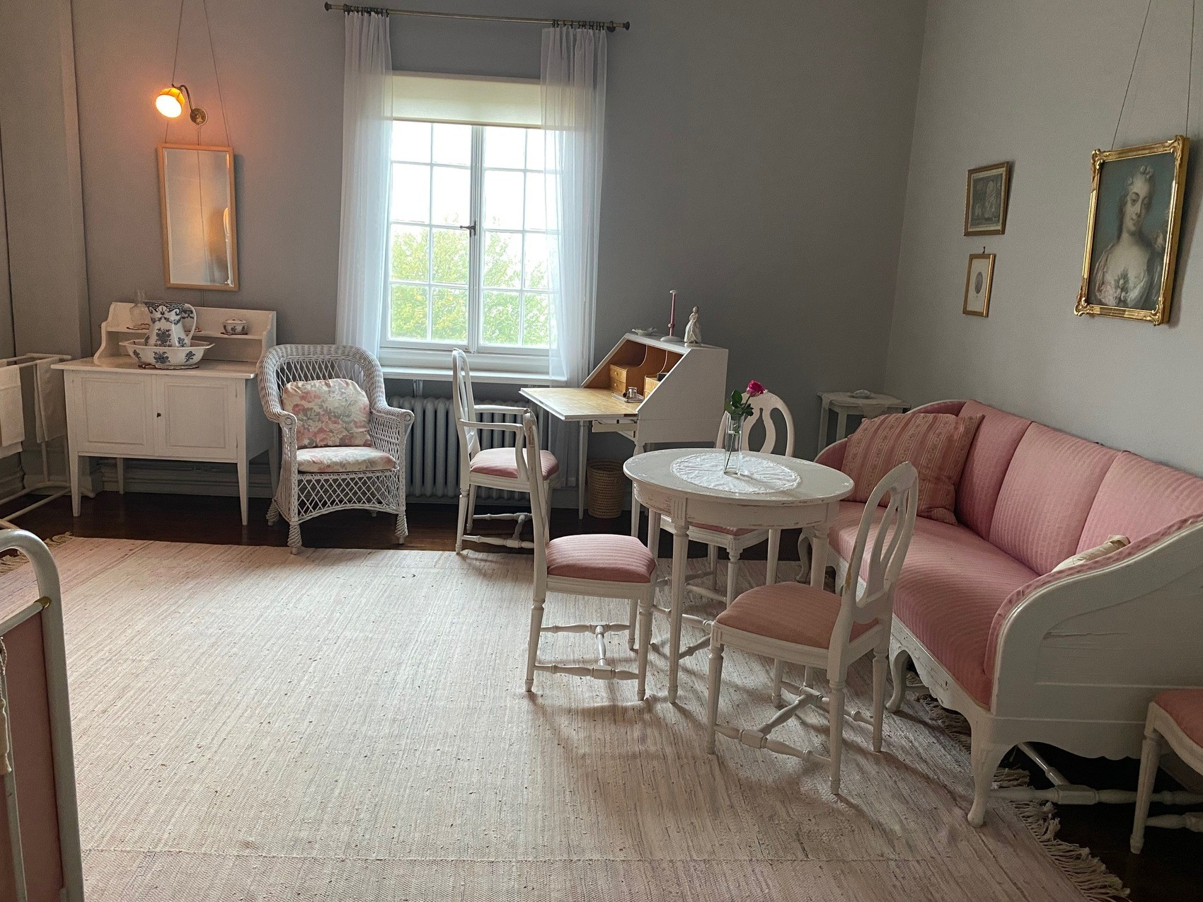 Ett rum med ljsugråa väggar och vitrosa möbler