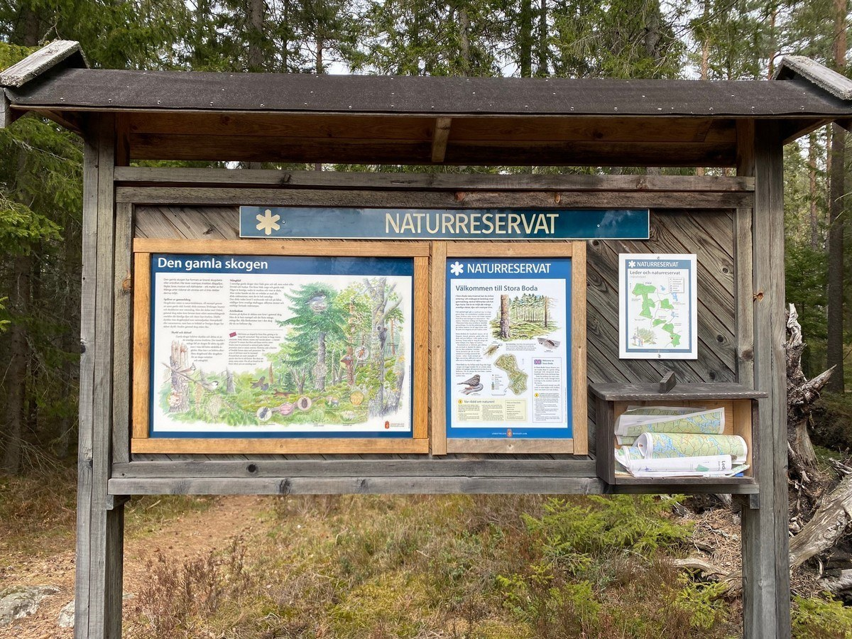 Stor informationstavla i skogsterräng