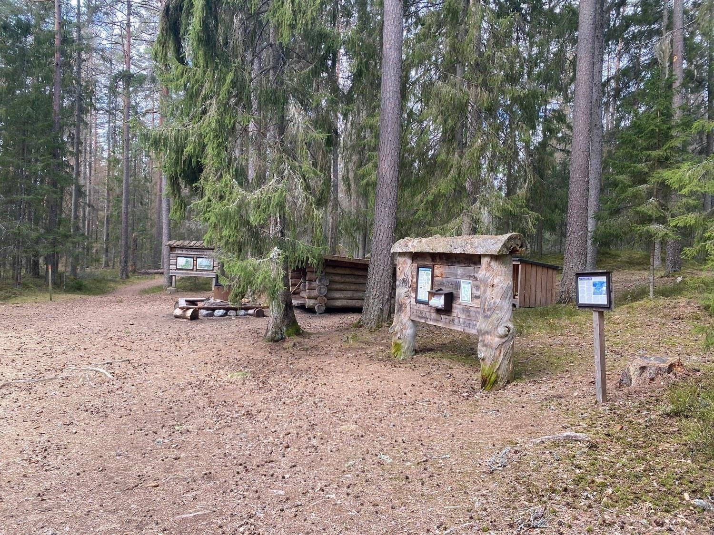 Glänta i skog med grill och stor skylt