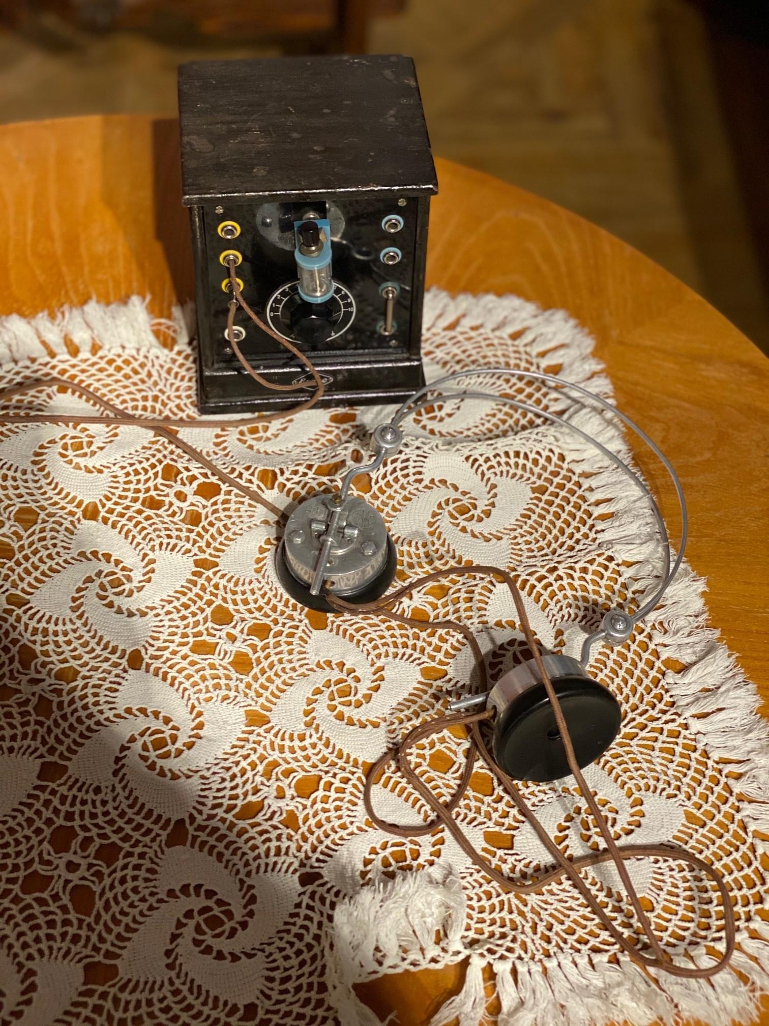 En mycket gammal telefon står på ett träbord med luren liggande på en brunvitfärgad duk.