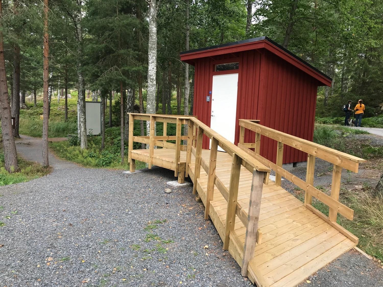 Röd liten toalettbyggnad med handikappvänlig ramp som leder upp till dörren.