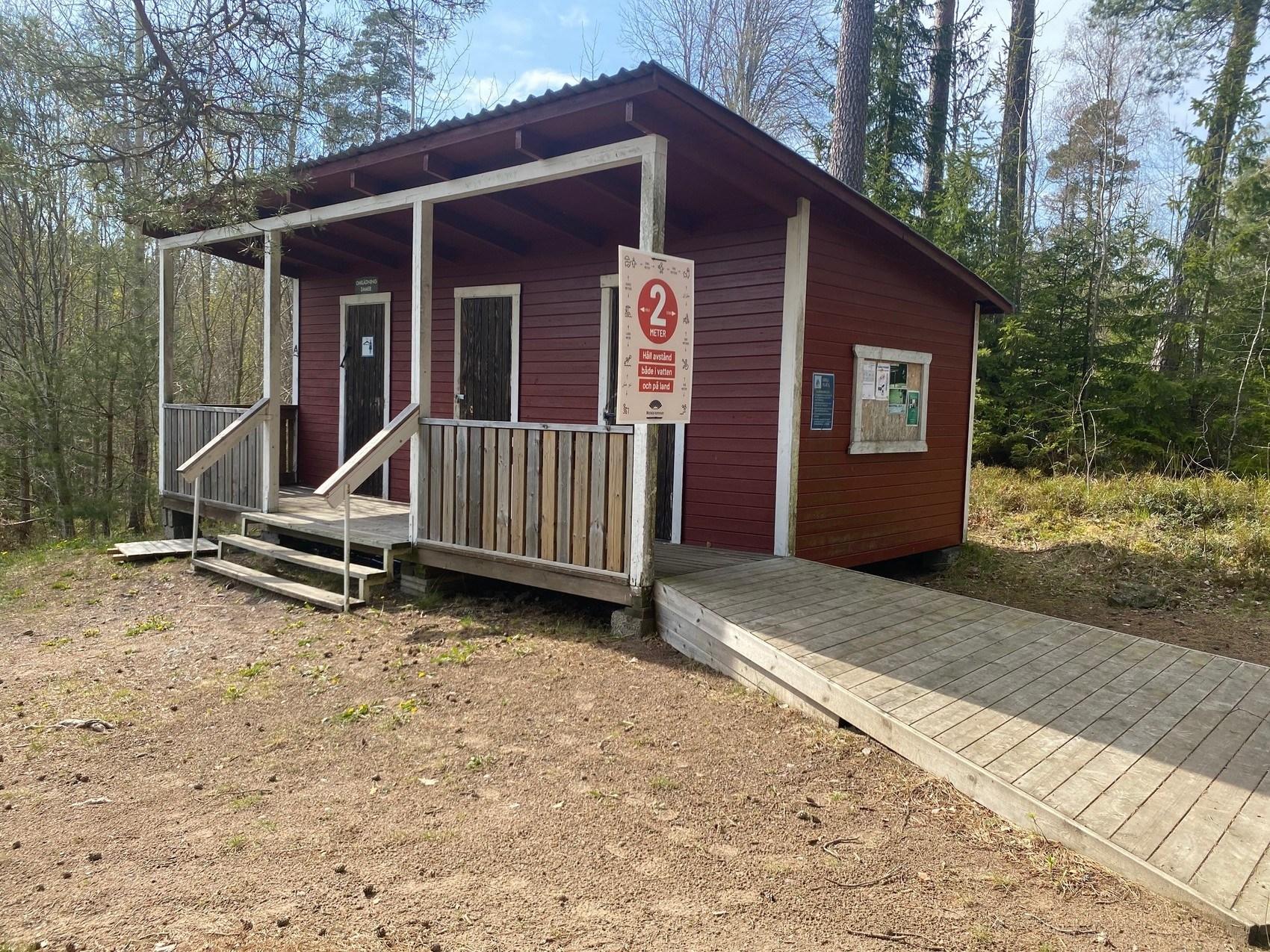 Röd toalettbyggnad med trappa och ramp som leder upp till dörrarna.