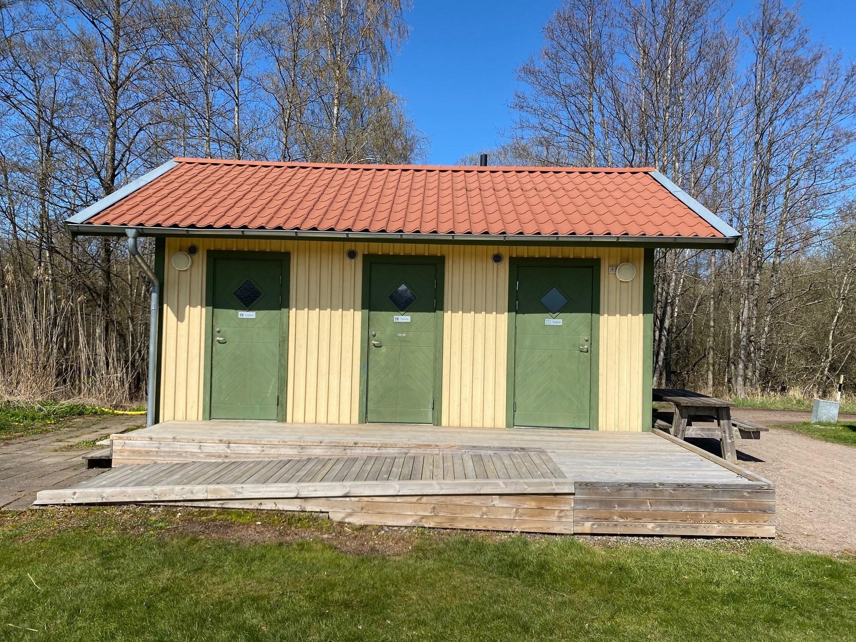 Gulbyggnad med tre gröna dörrar