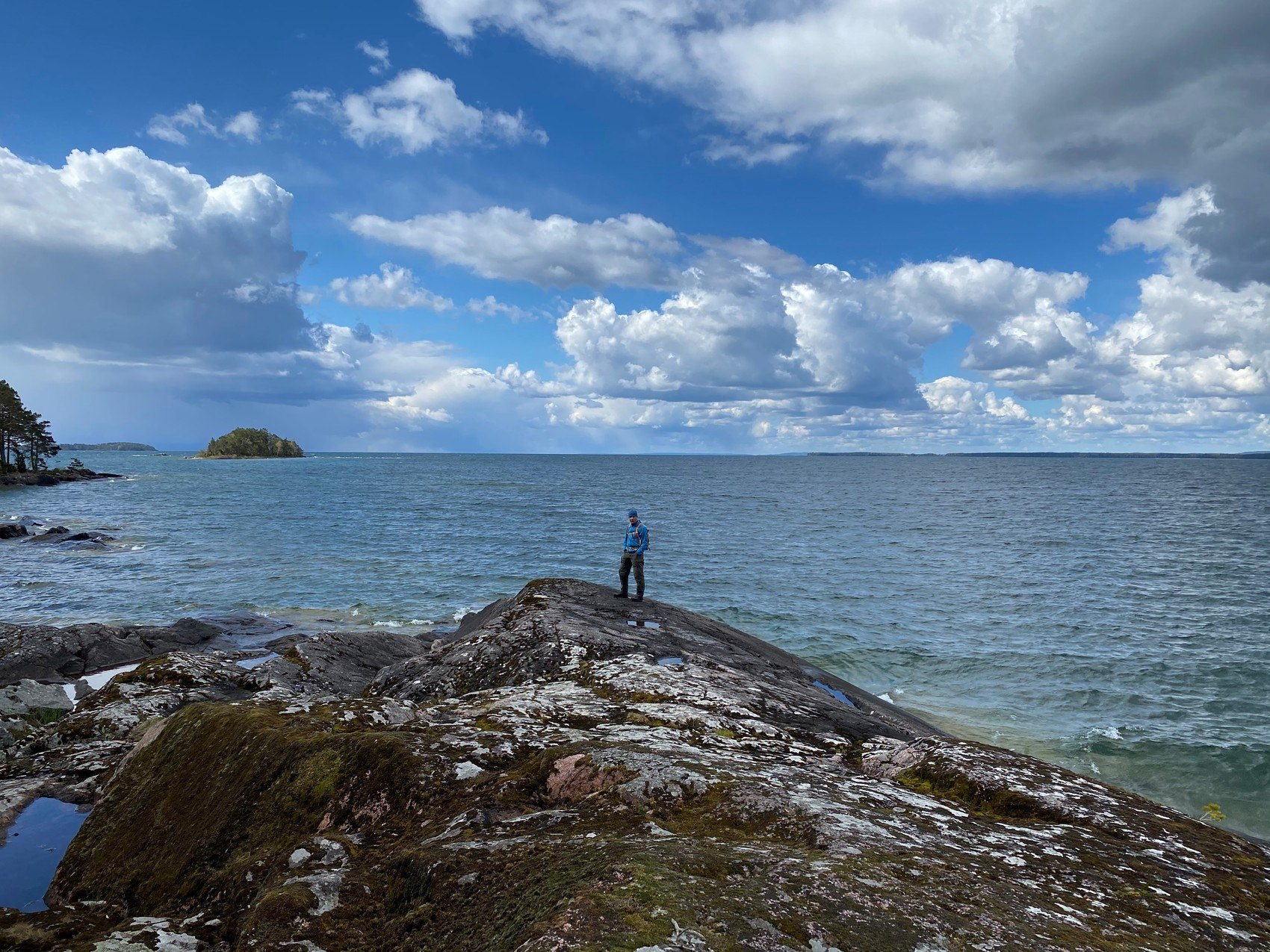 Vy över klipper och vatten. En person står på en klippa och tittat ut över vattnet.