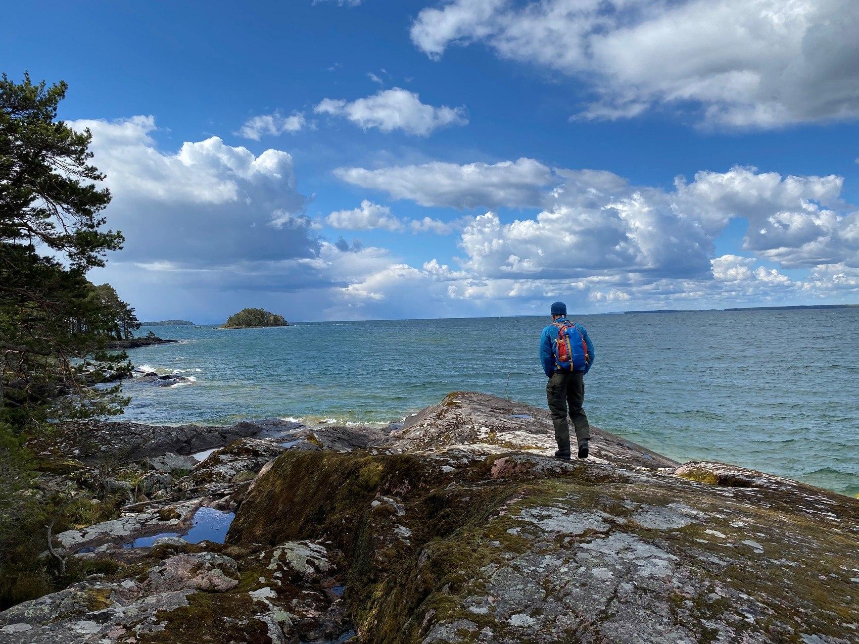 Person står på klippa och tittar ut över vattnet