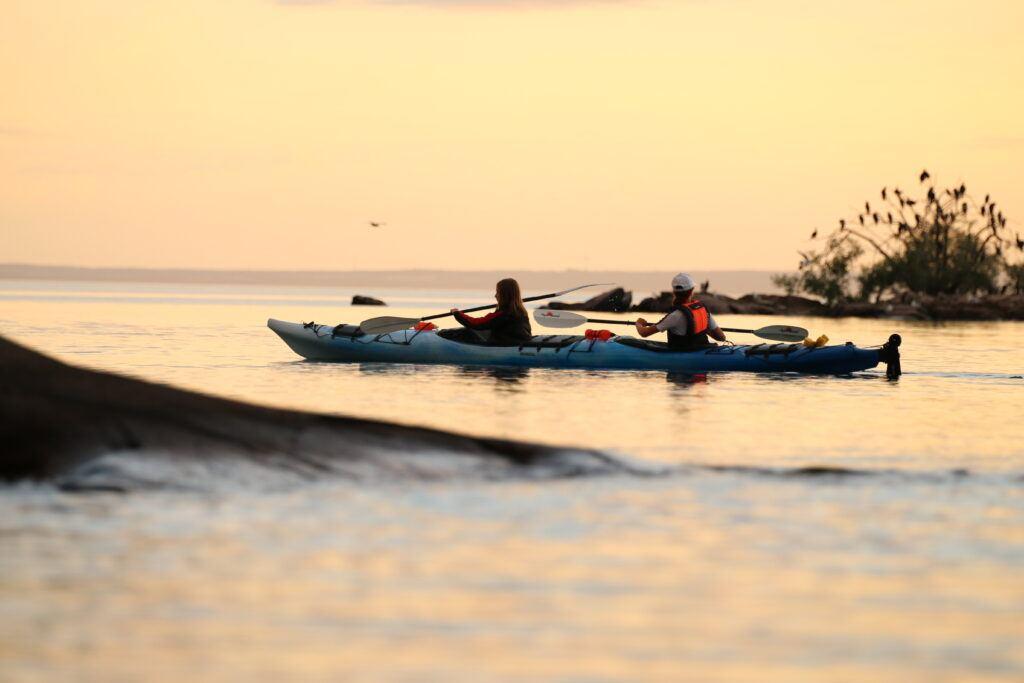Två personer paddlar kajak i solendgången
