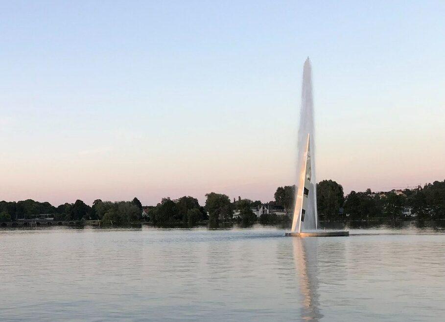 En spegelblank vattenyta, i horisonten skymtar en stadssilhouette och till höger i bild en skulptur som ser ut som en passare som sprutar vatten