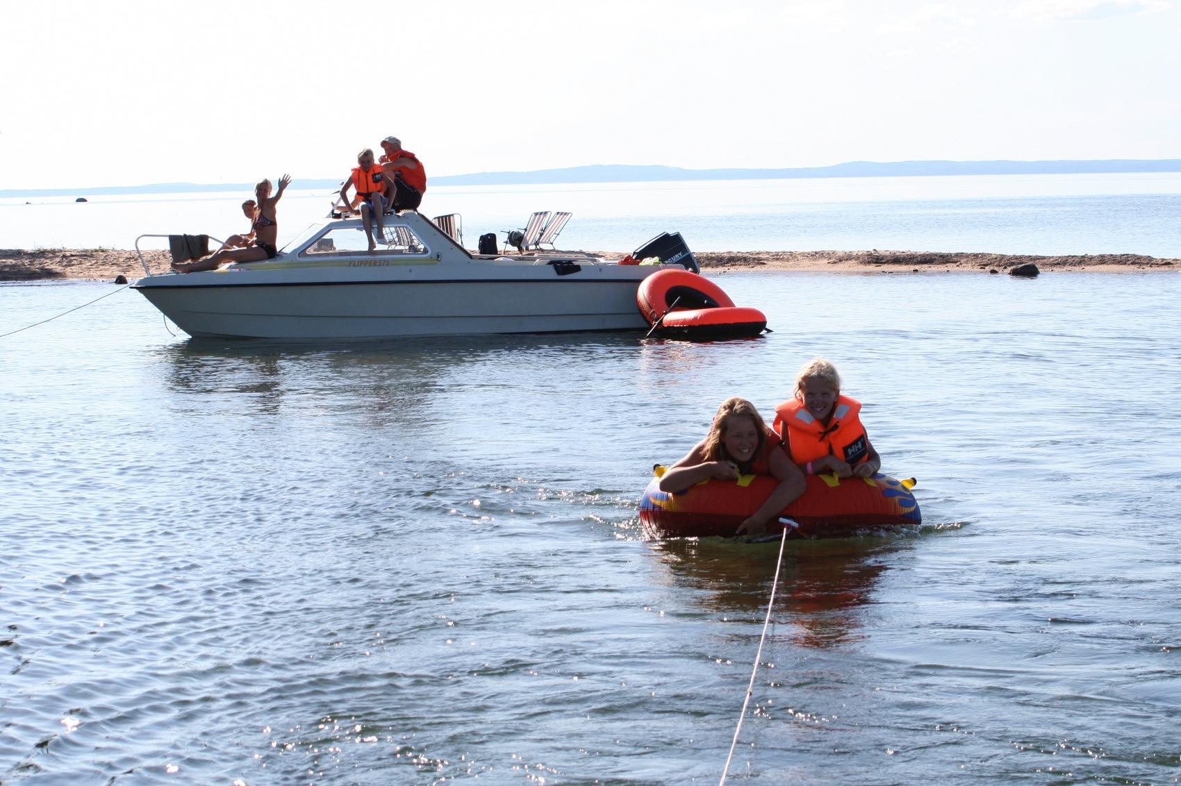 Två barn ligger på en flytande ring i vattnet kopplad till båt