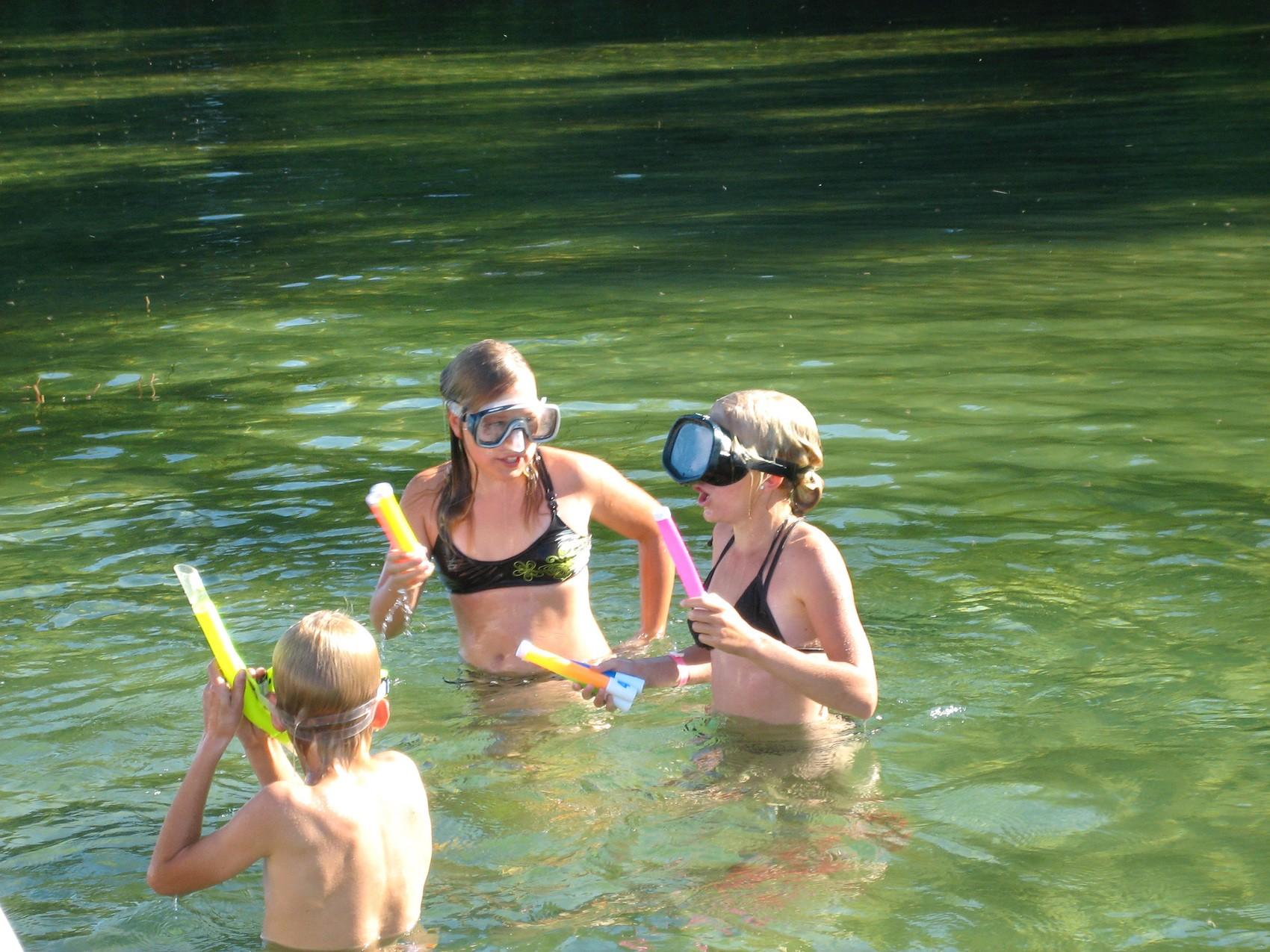 Tre barn med cyklop och snorkel står i vattnet