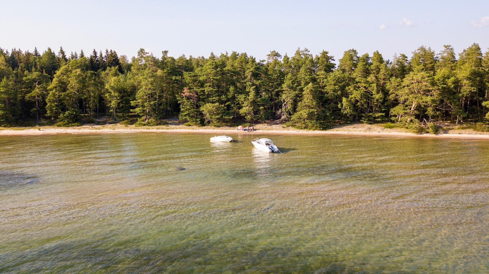 Foto taget från vattnet in mot land där två motorbåtar ligger vid en solig sandstrand