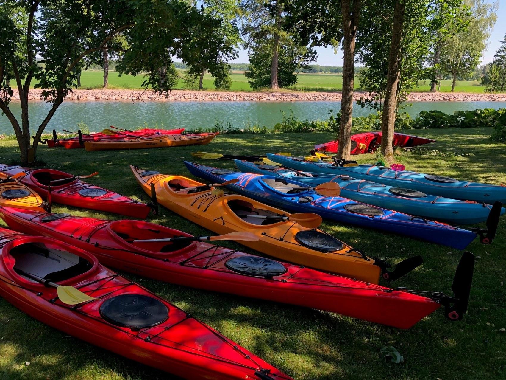 Röda, blåa och orangea kajaker ligger på gräset intill kanalen